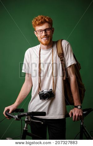 Young happy readhead bearded man with backpack and retro camera, standing on bicycle isolated over green background