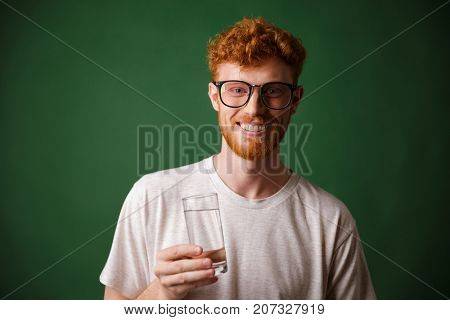 Cheerful readhead bearded man in glasses, holding glass of water, over green background
