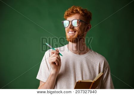 Close-up view of cheerful bearded young man in white tshirt holding a notebook and a pen, over green background