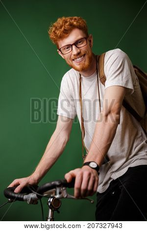 Young cheerful readhead bearded hipster with backpack and retro camera, standing on bicycle isolated over green background, ready to ride