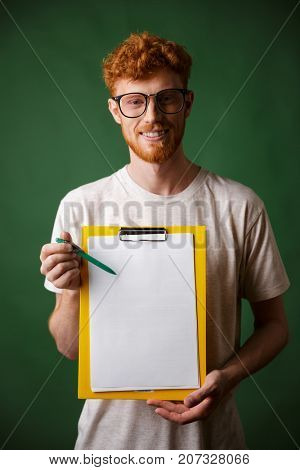Smart readhead bearded man in white tshirt showing folder with copyspace, looking at camera, over green background