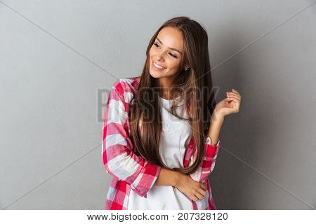 Portrait of a beautiful young woman in plaid shirt standing and looking away isolated over gray background