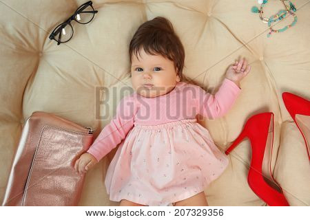 Cute baby girl with modern accessories lying on lounge at home