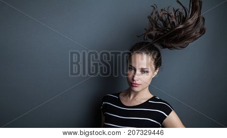 beautiful young woman portrait with ponytail in motion studio shot
