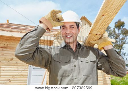 Skilled worker working at construction site and carries wood