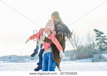 Father playing romp or roughhouse with daughter in winter