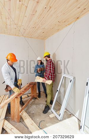Craftsmen cooperating and working as a team on new house