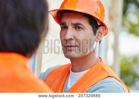 Man as construction worker with orange hardhat