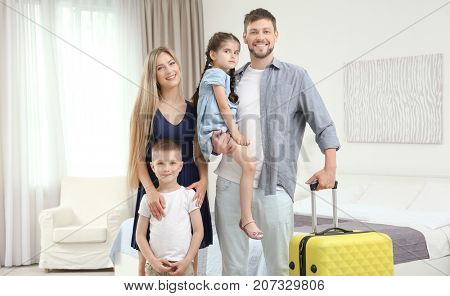 Family with luggage in hotel room