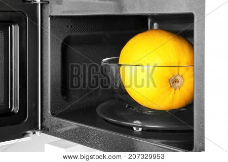 Glass bowl with ripe spaghetti squash in microwave
