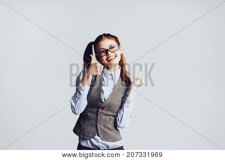 girl student in glasses shows her thumb