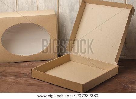 Cardboard boxes on a dark wooden background. Corrugated cardboard