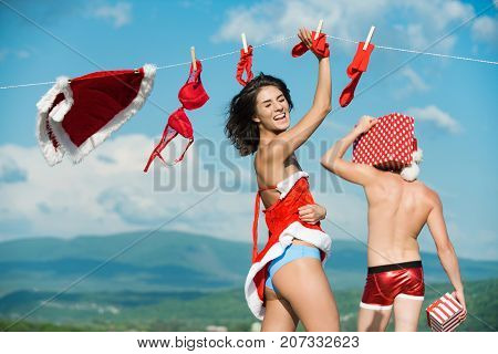 Laundry and dry cleaning. Couple in love of man and girl hanging clothes for drying. Christmas man and woman family. Xmas red costume on rope with pin. New year guy with muscular body on blue sky.