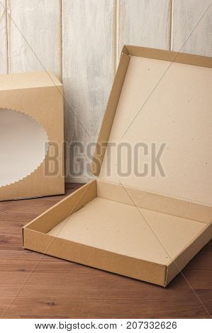 Cardboard boxes on a dark wooden background. Corrugated cardboard