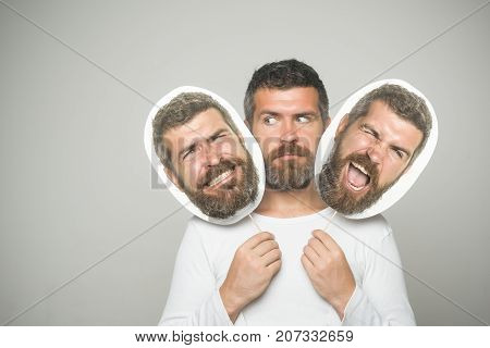 Man with long beard and mustache. Hipster with winking and serious face hold portrait nameplate. Feeling and emotions. Guy or bearded man on grey background. Barber fashion and beauty.