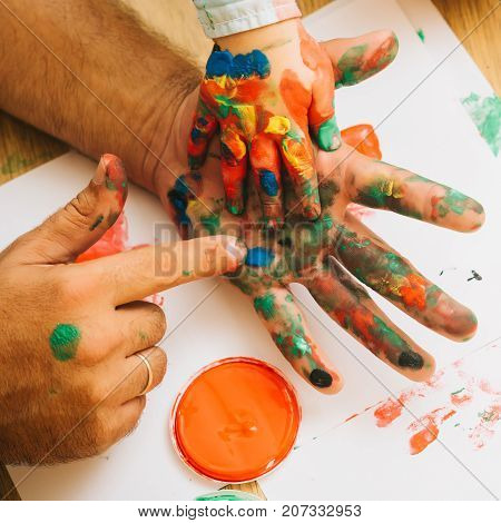 Fingers and hands drawing with multicolor paints on white paper. Arts and crafts. Handprint painting concept. Fathers day family love and care. Imagination creativity and freedom.