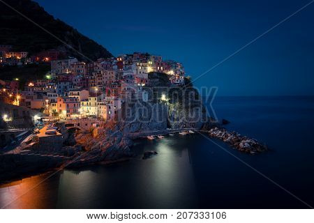 Stunning view of the beautiful and cozy village of Manarola in the Cinque Terre National Park at night. Liguria, Italy.