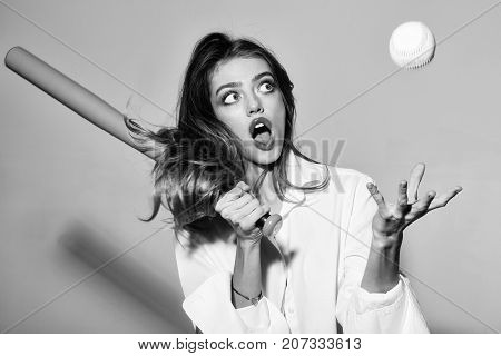 young pretty woman or cute sexy girl with beautiful long hair and red lips on adorable surprised face in fashionable white shirt holds green baseball bat or racket and ball on grey background