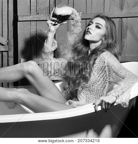 Attractive young sexual woman with long curly hair and straight slim body in knitted blue cloth sitting in white bath tab holding drinking glass with red liquid with smoke as elixir of beauty indoor