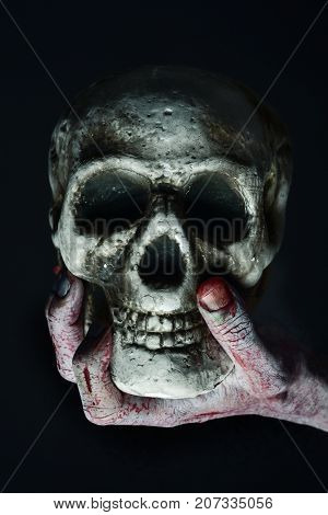 closeup of the scary hand of an undead man holding a skull against a black background