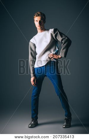 Men's beauty, fashion. Handsome male model posing at studio in modern clothes.