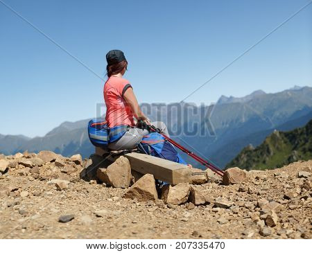 Picture from back of woman with sticks for sporty walk