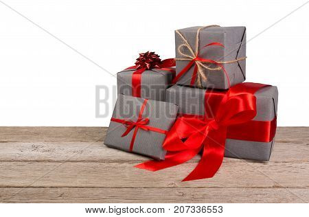 Gift boxes wrapped with gray paper and red satin ribbon on wooden table at white background. Modern presents for any holiday, christmas, valentine or birthday