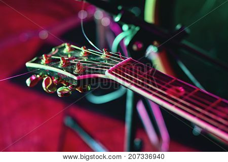 Closeup of guitar fingerboard at concert in colorful light