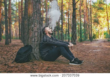 Vape man. brutal bearded young man having rest in forest and vaping an electronic cigarette. Lifestyle. Vape concept poster