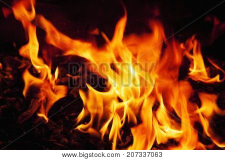 Red hot background of fire as a symbol of hell and eternal torment. Selective focus.