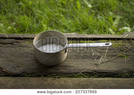 A ladle with clean water from a well in the nature against a background of grass