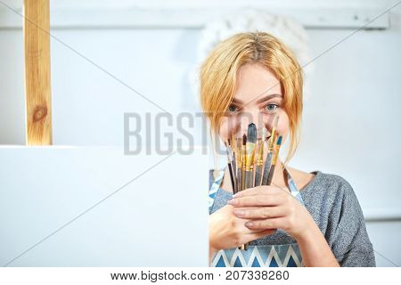 A cute smiling girl holding a paintbrush and a box with oil paints in hands and posing on the camera in own workshop. Close-up of paintbrush. Art concept.