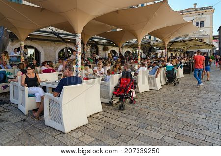 KOTOR MONTENEGRO - SEPTEMBER 8 2017: Unknown tourists rest in street cafe on Square of Arms in Old Town Kotor Montenegro