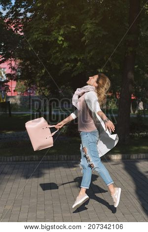 Young happy jumping woman with bag on the street. Easiness concept.