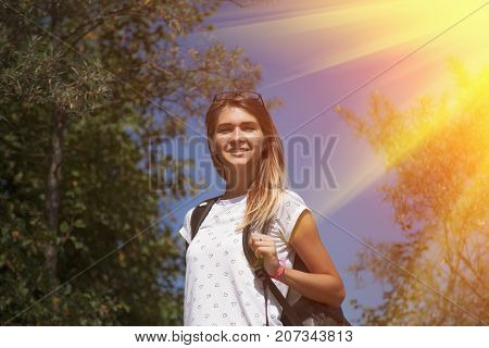 Young beautiful woman with backpack hiking in the woods and looking at amazing woods and mountains (adventure holiday travel concept)