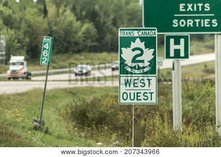 Signpost with green sign of the Trans Canada 2 Highway westdirection connecting the east- and west coast