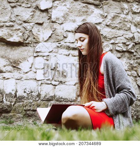 Girl student learning on the grass outdoors (education self-development self-organization time management concept)