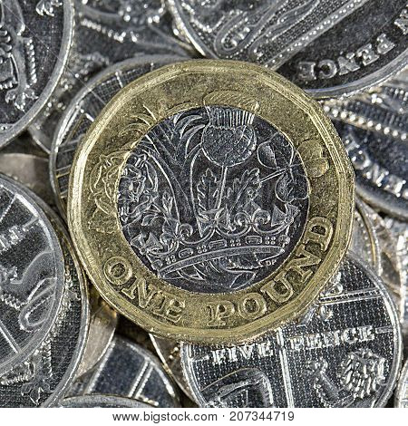 Close up of a one pound British coin on five and ten pence pieces in a square format - British Currency