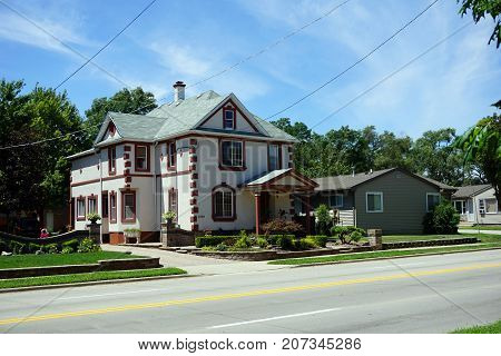 JOLIET, ILLINOIS / UNITED STATES - JULY 25, 2017: A large, two story, single family stucco home, on Broadway Street, in Joliet.