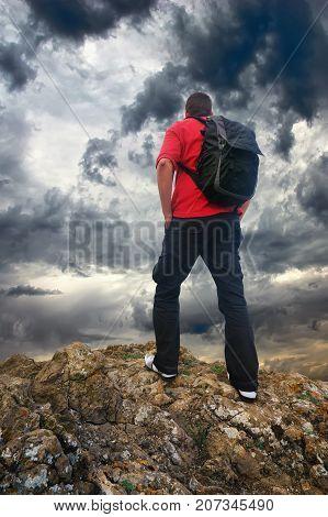 Man on the mountain edge. Tourist on the mountain edge and dark sky