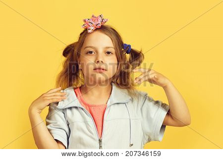 Girl With Concentrated Face Isolated On Warm Yellow Background