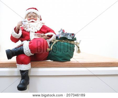 Fabric maché Santa sitting on a shelf, with sac of gifts, eating, to left of picture
