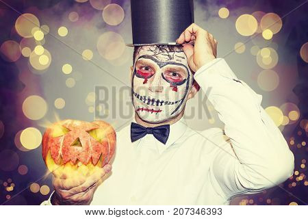 portrait of man for Halloween party. Beautiful halloween man with burn pumpkin in hand. Halloween party concept. Bloody theme on Halloween