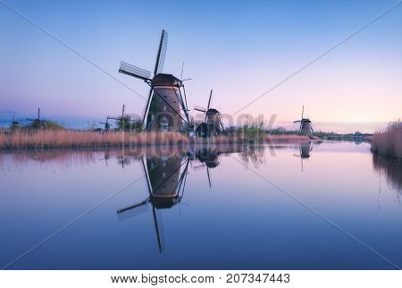 Windmills And Clear Blue Sky At Sunrise In Kinderdijk, Netherlands