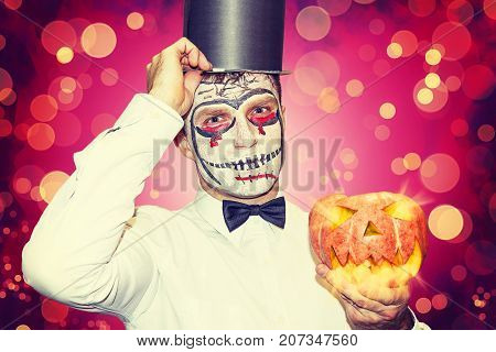 Halloween party theme. Portrait of man in mask for Halloween in black hat and burning pumpkin in hand. Night halloween party concept. man dressed in Halloween costume. He is ready for Halloween party