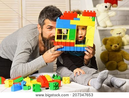 Family And Childhood Concept. Boy And Bearded Man Play Together