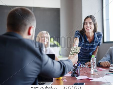 Young professional team. Pretty girl receives a salary. Group of young modern people in smart casual wear having a brainstorm meeting while sitting behind the glass wall in the creative office. Business concept.