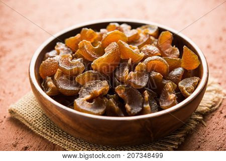 Ayurvedic Amla Candy, which is dried and salty-sweet or chatpata in taste and digestive. Served in a wooden bowl, selective focus