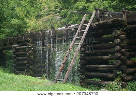 Log water trough with water spilling over,