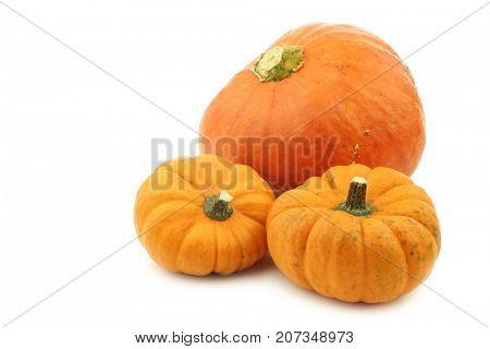 three orange decorative pumpkins on a white background
